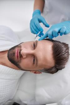 Косметолог держит палец на виске клиента зрелого мужчины после инъекции филлера для лифтинга кожи