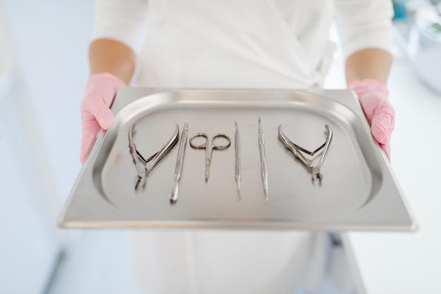 Косметолог держит металлический поднос с маникюрным и педикюрным оборудованием, косметологическими инструментами. п