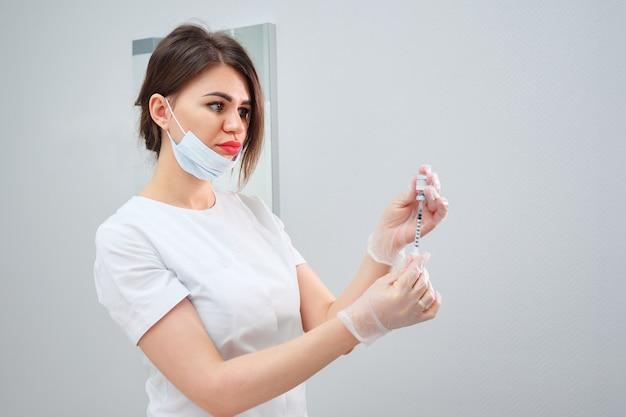 Косметолог держит шприц, наполненный гелем