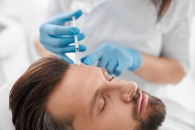 Косметолог в перчатках делает инъекцию наполнителя в лоб зрелой пациентке в салоне красоты