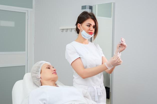 마스크를 쓴 미용사는 의료 피부 치료를 수행하기 위해 생체 적합성 약물로 채워진 주사기를 들고 있습니다
