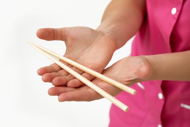 ピンクの医療制服を着た美容師は、竹のマッサージスティックを手に持っています。小規模なビジネス。スパサロン。美容業界。アンチエイジング手順。マッサージトリートメント。ライフスタイル。