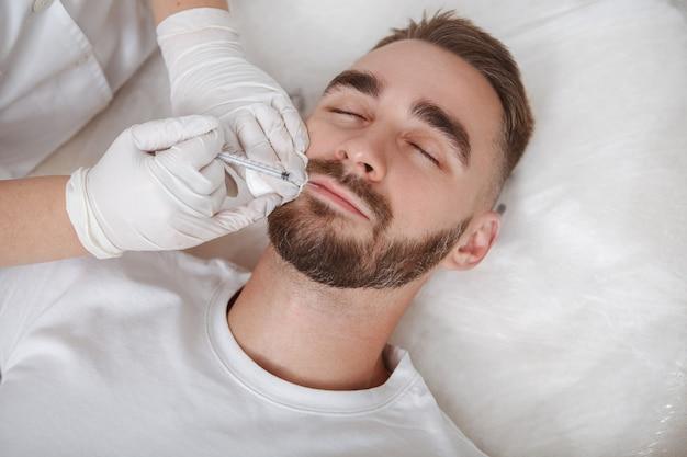 남성 고객의 피부에 얼굴 필러를 주입하는 미용사