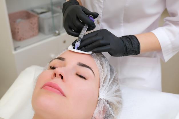 미용사는 젊은 여성의 피부에 주사기를 주입합니다.