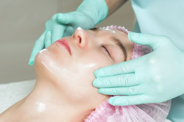 Cosmetologist is applying a white cream on woman's face.