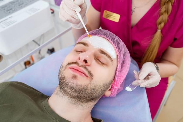 美容師は美容院でブラシを使って男の顔に白い保湿マスクを適用しています、顔のクローズアップ。美容業界のコンセプト。男はソファに横たわっています。スパの手順を作る美容師の女性。