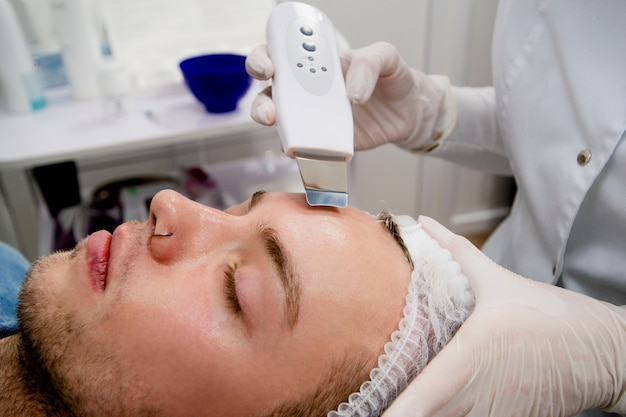 Cosmetologist is cleaning man's face from acne and scars using ultrasonics.