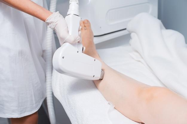 Косметолог делает лазерную депиляцию ноге женщины.