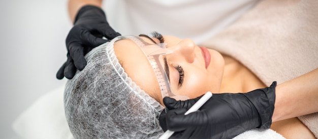 Cosmetologist is measuring with ruler the brows of young caucasian woman before permanent makeup tattoo