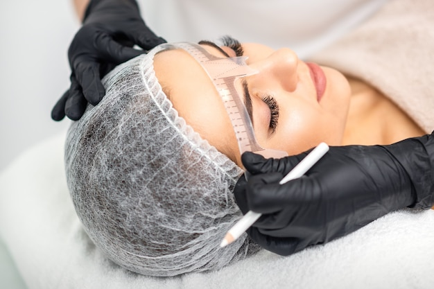 Косметолог измеряет линейкой брови молодой кавказской женщины перед татуировкой перманентного макияжа