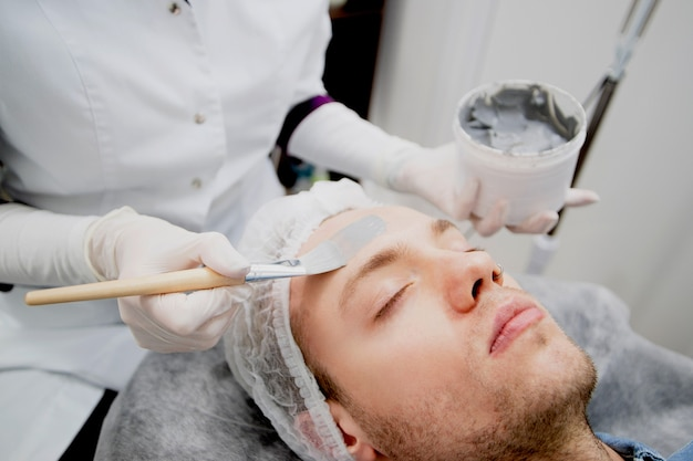 Cosmetologist is putting black mask on the young man's face in the beauty salon.