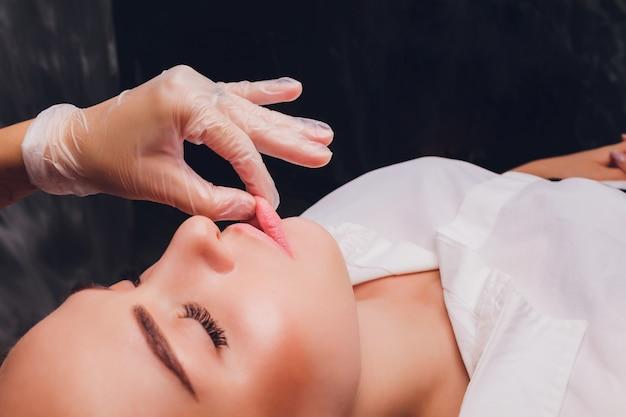 美容師は、患者の顔の筋肉の頬マッサージを行います。