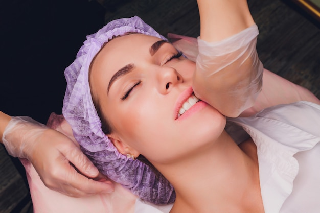 Cosmetologist makes a buccal massage of the patient's facial muscles.