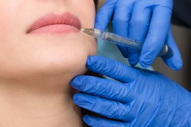 Cosmetologist makes lip augmentation procedure in a beauty salon. the beautician injects hyaluronic acid into the lips to increase the volume.