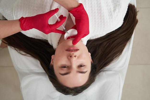 Косметолог делает липолитические уколы для сжигания жира на подбородке против двойного подбородка. женский