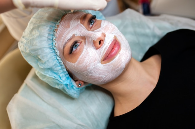 Cosmetologist makes the mask beautiful girl
