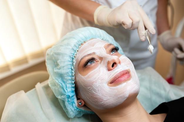 Косметолог делает маску красивой девушке