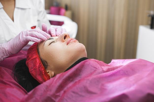 彼女の患者とフェイスマスクに顔のマッサージを行う美容師。ビューティーサロンでのアンチエイジング。