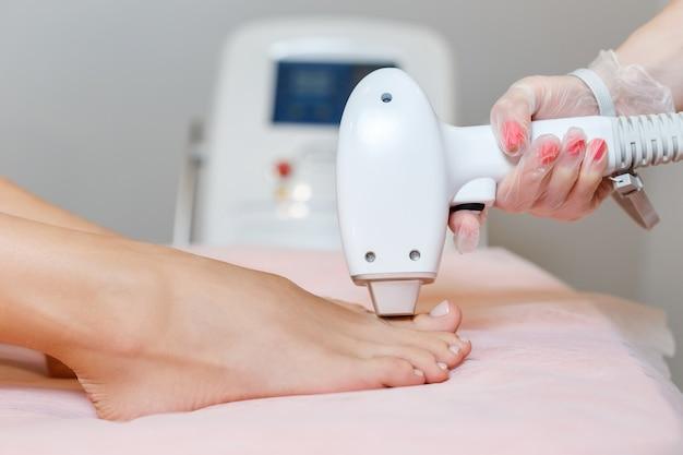 Косметолог делает лазерную эпиляцию на ногах женщины