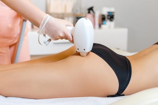 Косметолог делает лазерную эпиляцию на ягодицах молодой женщины