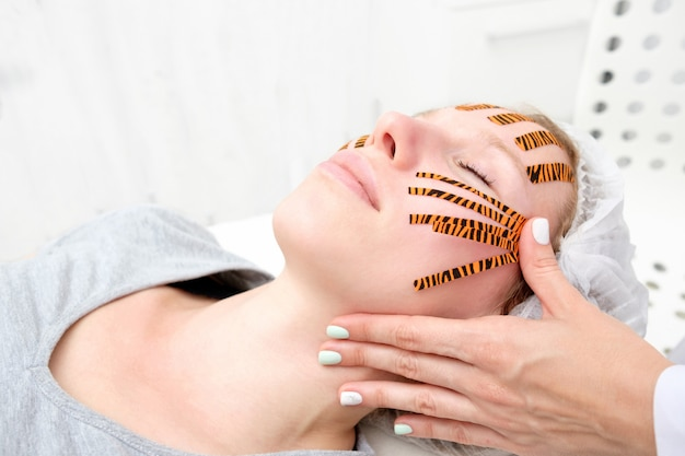 Cosmetologist making taping face procedure using tiger colored tapes in beauty parlor