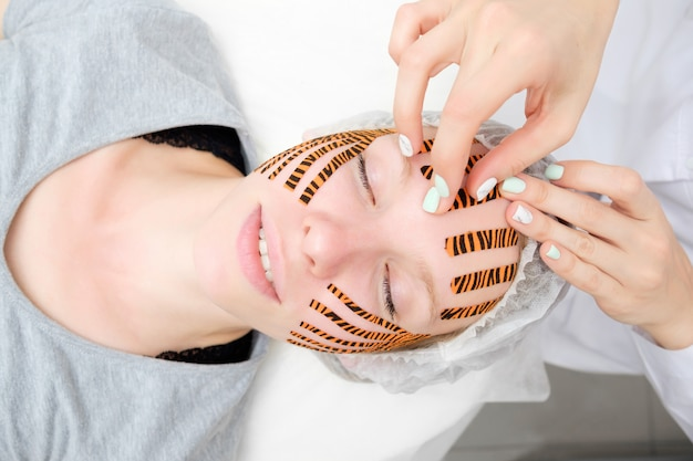 Cosmetologist making taping face procedure using tiger colored tapes