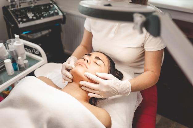 Косметолог массирует лицо клиента
