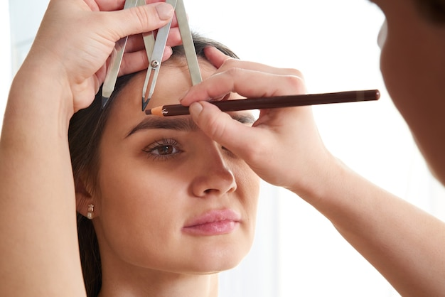 Cosmetologist measures the proportions of the eyebrows with the ruler.