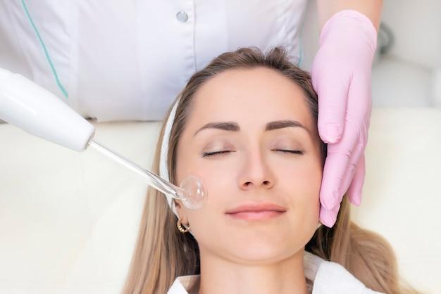 Косметолог проводит процедуру импульсного тока для лица молодой женщины.