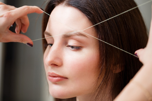 美容師は糸でクライアントの眉毛を摘み取ります。閉じる