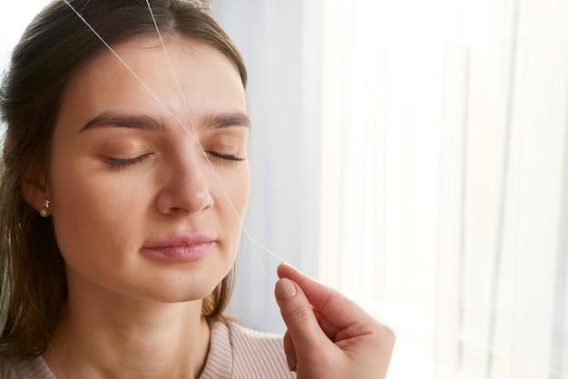 Косметолог выщипывает брови клиентке на нитке в салоне красоты