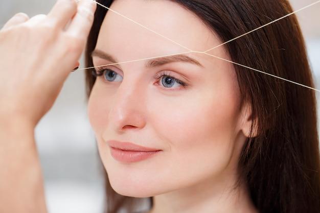 美容師が糸でクライアントの眉毛をむしる