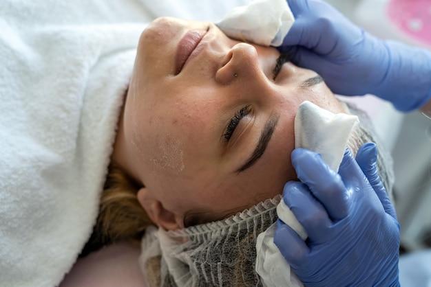 美容クリニックのテーブルに横になっている若い女性の手順に直面する美容師。美容業界のコンセプト