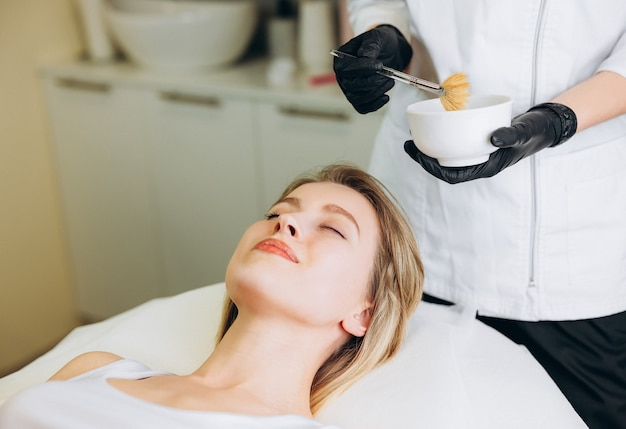 Cosmetologist puts chemical peeling of the woman's face with brush.