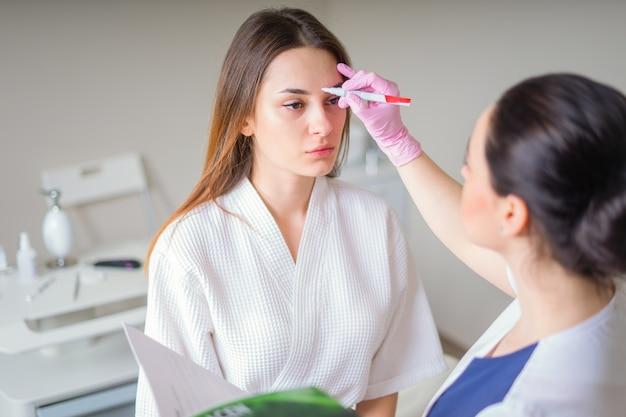 Косметолог готов нарисовать линии маркером на лице пациента