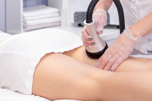 Косметолог уменьшает целлюлит на бедрах пациентки, используя ультразвуковой кавитационный аппарат