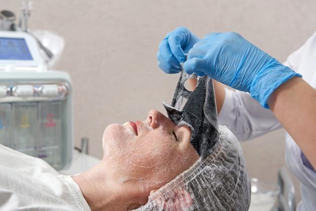 美容院で患者の顔から黒い酸素バブルマスクを取り除く美容師