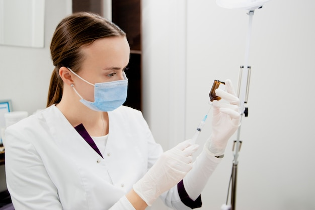 Cosmetologist's preparing to make injections to man's face to remove scars and wrinkles and make it smooth and young.