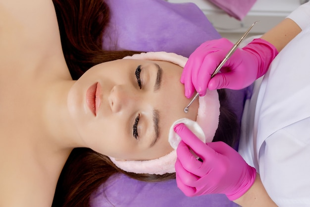 Cosmetologist at spa beauty salon doing acne treatment using mechanical instrument. concept of medical treatment of rejuvenation and skincare.