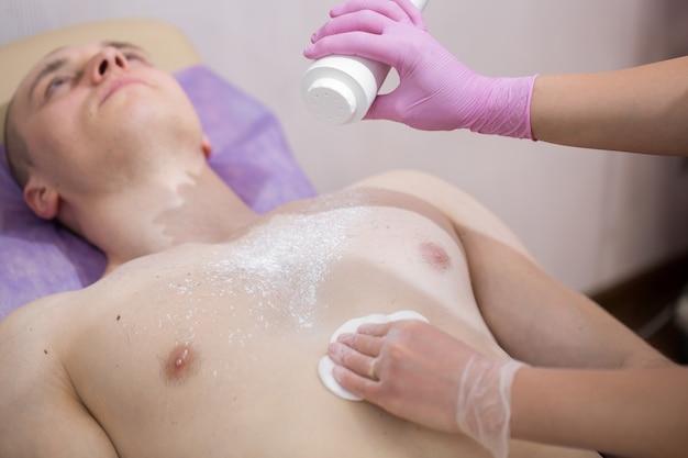 Косметолог посыпает сахарной пастой тальк или пудру мускулистого мужчины перед процедурой эпиляции.