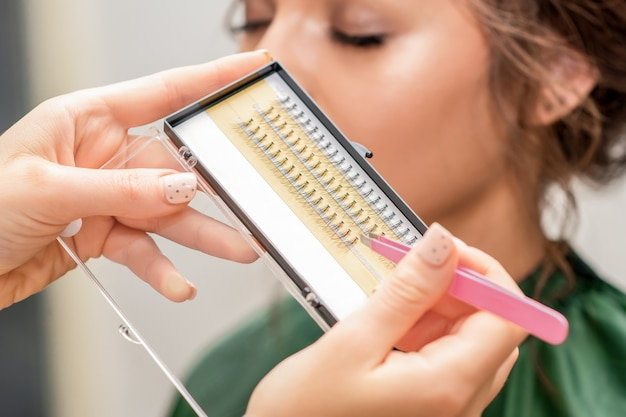 Cosmetologist takes artificial lashes with tweezers.
