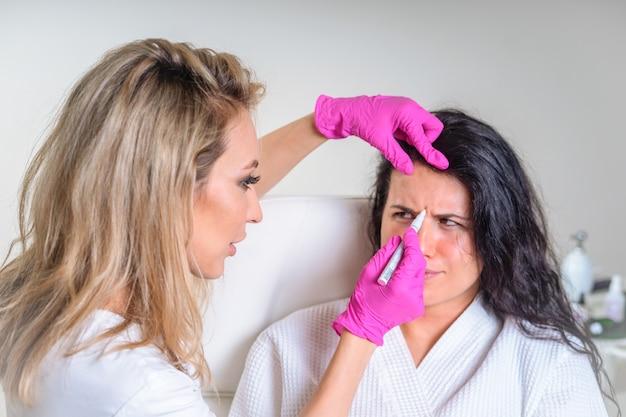 스파 살롱에서 미용 치료 전에 환자 얼굴에 얼굴 마커를 사용하는 미용사
