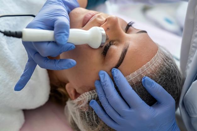 美容spaサロンで手技リフティングセラピーマッサージを行う超音波キャビテーションマシンを使用する美容師 Premium写真
