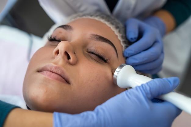 Косметолог с помощью ультразвуковой кавитационной машины делает процедуру лифтинг-терапевтического массажа