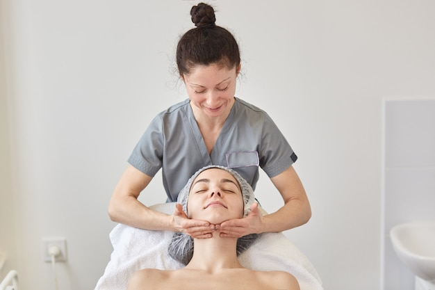 Cosmetologist wears gray gown massaging patient face.