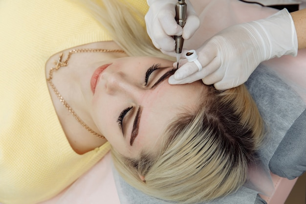 Cosmetologist in white gloves applying make up with machine for woman in beauty salon