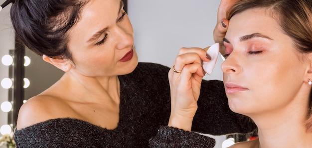 女性のメイクアップを拭く美容師