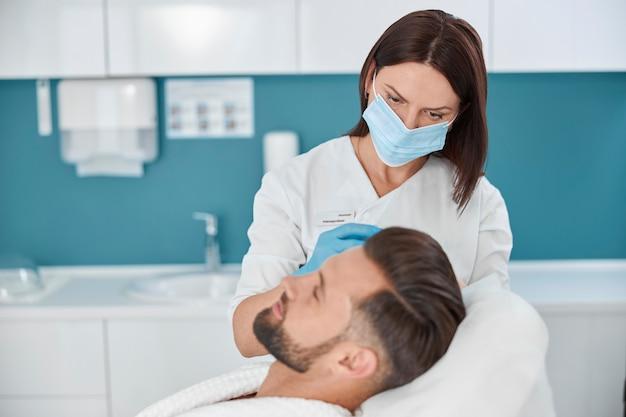 Косметолог с одноразовой маской делает инъекцию лекарства клиенту во время антивозрастной мезотерапии