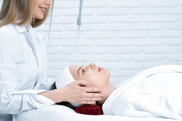 Cosmetologist working and doing face massage in salon