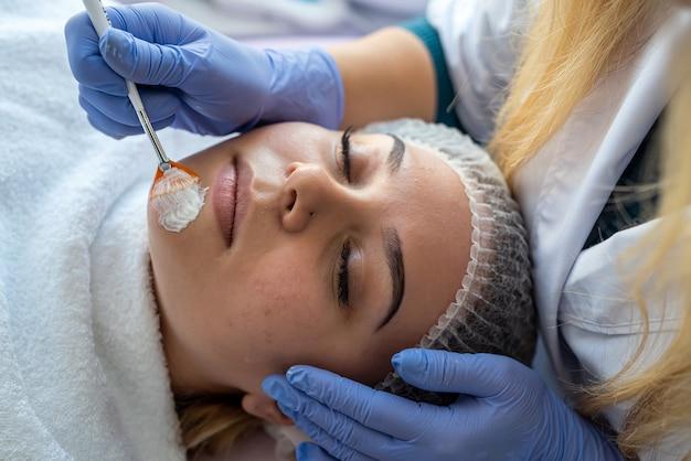 미용사 손 치료 치료 및 스킨 케어를 위해 얼굴 젊은 여성에 보습 크림을 적용합니다. 깨끗하고 부드러운 바디 피부 컨셉